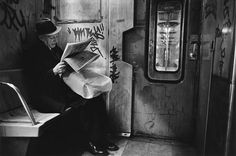 Richard Sandler - New York in the 1980s, 'Subway Noir': This black-and-white image shows a man reading the paper in a grey and grim-looking subway carriage