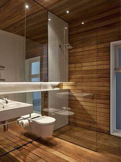 Inodoro suspendido y sisterna oculta en baño con mucha madera