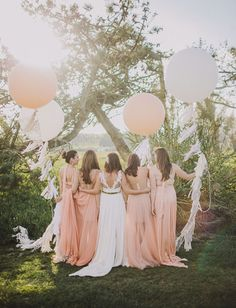 Peach bridesmaids with geronimo balloons and tassels
