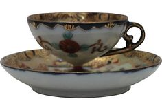 """Japanese Demitasse Cup & Saucer Vintage Japanese demitasse cup and saucer detailed with a geisha and gold floral designs, butterflies, and a fan. Dimensions: cup, 3""""Dia x 2.25""""H; saucer, 5""""Dia x 1""""H."""