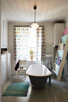 rustic cabin bathroom, ladder towel holder, built in cabinets, wood ceiling, painted wood floors, clawfoot tub