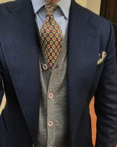 A contrasting cardigan, even in a conservative color, makes a big difference in your visual profile.  I choose brighter colors to go along with the shirt or tie.  Pocket square then should match either shirt, cardigan, or the secondary color in the tie (not the primary color)