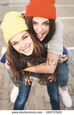 Two young hipster girl friends together having fun. Outdoors, lifestyle. by Kaponia Aliaksei, via Shutterstock