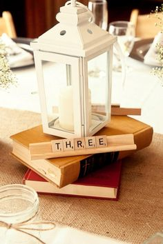 Wedding centerpiece with vintage books and lanterns. Add succulent table number and picture frame.  Garnish with orchids and baby's breath.