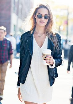 A white v-neck sweater dress is worn with leather jacket, simple necklaces and sunglasses.