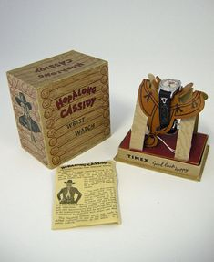 This 'Hopalong' Cassidy character wrist watch, designed specifically to be worn by children, was manufactured by Timex, probably at their factory in Dundee, Scotland, in the mid-1950s. It retains its original instruction booklet and guarantee, and is still in its original cardboard box, printed to resemble a log cabin and with a saddle-shaped presentation support for the watch to match with the cowboy theme.