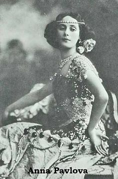 1915 (ca) Russian ballet dancer Anna Pavlova, seated in a chair, poses in an elaborate silk costume featuring jewels and bangles, a jeweled headband, and flowers in her hair.