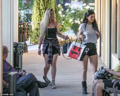 Grungy: the reality star Kylie Jenner and her friend was wearing black leather shorts, a white tee, black boots and a Celine Colour blocked bag.