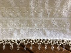 Toalha de lavabo na cor branca, com bordados em pedrarias e bordado inglês.  Medida 30x45cm.
