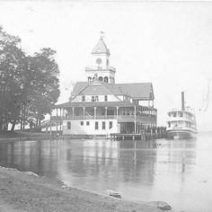 Chautauqua Institution - Steamboat at the Old Pier Building in 1890 - Between 1911 and 1916 the Pier Building had its bell tower removed as the bells were too much weight for the building's pilings/underpinnings. The chimes were installed in the newly built Miller Bell Tower. The Old Pier Building was eventually replaced by the New Pier Building which is now the College Club. Photo credit: L.E. Walker