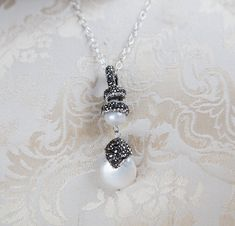 Unique sparkly black diamond crystal paved white freshwater pearl pendant, delicate organza necklace or sterling silver, long drop pendant. It measures about 55mm in length. The larger coin pearl is 15mm x 20mm. You can choose to buy it with a delicate white organza necklace 42cm long + 5cm extension, or a solid sterling silver necklace of 56cm.  ***************************************************************  Your purchase(s) will come wrapped in a pretty organza gift bag or in a beautiful p...
