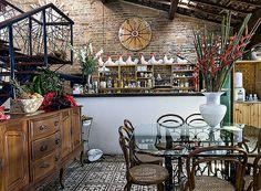 Living e cozinha integrados com algumas paredes de tijolos descascados unindo-se aos típicos ladrilhos hidráulicos dos pisos, com diferentes padrões coloridos. - Casa e Jardim
