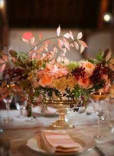 The low centerpieces will be silver compotes filled with a mix of greenery and foliages, blush spray roses, pink astrantia, yellow craspedia, orange ornithogalum, jasmine vine, and white-green Queen Anne's lace surrounded by mercury glass votives.