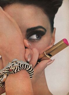 Wilhelmina Cooper wearing a diamond, ruby and enamel zebra bracelet and holding a pink lipstick from Vogue 1964
