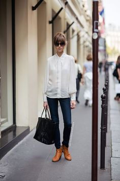 Shop this look on Lookastic:  http://lookastic.com/women/looks/sunglasses-dress-shirt-skinny-jeans-tote-bag-ankle-boots/9922  — Black Sunglasses  — White Silk Dress Shirt  — Navy Skinny Jeans  — Black Leather Tote Bag  — Tan Leather Ankle Boots