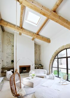 The rattan swing is so casual and playful! But the room overall is quiet with the neutral bright backdrop and the natural wooden beams. The arched window painted out black is awesome too.