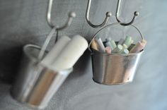 Small pails for chalk. In our kitchen these could hang on the bar below the blackboard.
