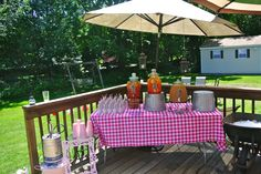Drink set up. Keg in a pink bucket, milk jar party favors, glass drink dispensers, pink solo cups, on a hot pink checkered table cloth.