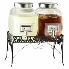 """3-piece beverage dispenser set. Includes 2 glass dispensers with a 1-gallon capacity and 1 metal stand.      Product: 2 Beverage dispensers and 1 standConstruction Material: Glass and metalColor: Clear and blackFeatures: 1 Gallon capacity eachDimensions: 16"""" H x 12"""" W x 7"""" D (overall) Cleaning and Care: Hand wash"""