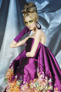 John Galliano kicked off the Spring/Summer Haute Couture shows in Paris with his collection for Christian Dior, displaying wild, futuristic designs in bold, bright colors, topped off with loads of big hair, wild, geometric makeup, and even feathered