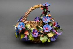 Superb basket centerpiece of purple petunias in Capodimonte porcelain finely worked. Each flower is reproduced in detail by the artist and it is then set on a beautiful basket, which is also entirely woven by hand.         Dimensions cm. 18x25