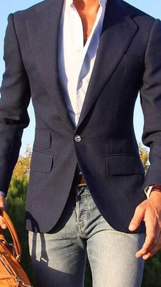 This combination of a navy blue blazer jacket and grey jeans is perfect for a night out or smart-casual occasions. Shop this look on Lookastic: https://lookastic.com/men/looks/navy-blazer-white-long-sleeve-shirt-grey-jeans/17919 — White Long Sleeve Shirt — Navy Blazer — Grey Jeans — Tan Leather Tote Bag
