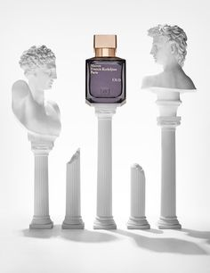 Maison Francis Kirkdjian fragrance bottle shot creatively for editorial with greek statues on top of columns. Creative still life photography shot by London based photographer Josh Caudwell.