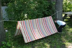 A tent made with a length of rope secured beteen two trees an a sheet draped over the top. How effective and simple!