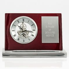 Piano Skeleton Clock W/Plate and Pen  $100  This handsome clock is the perfect addition to any desk at home or at the office. The combination of colours and finishes add to its design. The base has a slot designed to safely hold the pen for easy access.