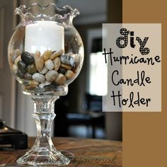*DIY Dollar Tree Hurricane Candle Holder* You will need 1 candle stick, 1 round scaloped bowl, 1 bag of craft rocks, super glue or carft glue and 1 candle.Glue round bowl to the top of the candle stick then add the craft rocks and candle. Hurricane Candle Holders, Diy Candle Holders, Diy Candles, Beeswax Candles, Wine Glass Candle Holder, Hurricane Vase, Candle Art, Dollar Store Hacks, Dollar Stores