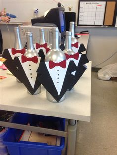 My school's prom theme is black tie affair. These are the center pieces to the tables. There will be a red carnation coming out of each one. They are super easy to make all you do is spray paint wine bottles then cut out different colors of card stock to make the tux. Very cute decoration.