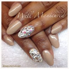 Nude gel nails with a jeweled nail.