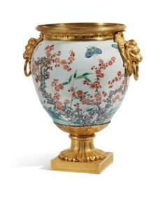 LOUIS XVI MOUNTED VASE Around 1770 Porcelain of the Famille Verde, China, Qing Dynasty, Kangxi Period (1662-1722), the gilded and gilded bronze mount, the butterfly-decorated body fluttering over bamboo and prunus in bloom, the ornate border of channels, loops made of lion's muzzles, the pedestal formed of alternating flutes of leaves, the base with square section.