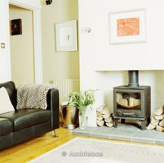 images of rooms with modern wood stoves | ... on black leather sofa beside wood-burning stove in modern living room