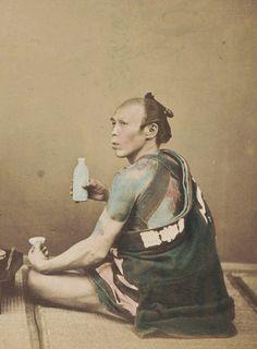Hand-colored photo of man drinking sake.  Circa 1880's, Japan.  Photographer Kozaburo Tamamura