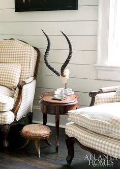 A pair of check-covered antique club chairs and an antelope antler stand create a striking grouping in this French-inspired abode.