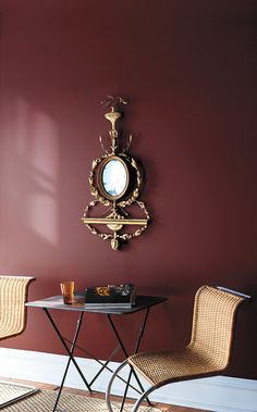 A sitting room features a delicate gunmetal grey table flanked by two contemporary ratan chairs underneath an elaborate wall hanging. - Experience Century Red Mahogany C9