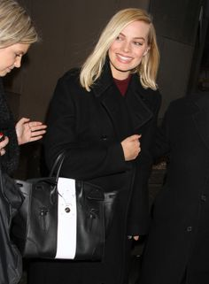 The Wolf of Wall Street star Margot Robbie carried the Ralph Lauren Collection Spring 2014 Soft Ricky Bag in black calfskin with single white stripe and silver hardware