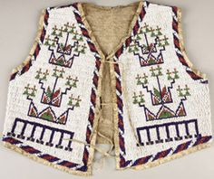 A Sioux boy's beaded hide vest, circa 1900, sinew sewn and lane-stitched in various shades of opaque and translucent beads, each side with intricate geometric motifs.