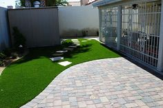 I love how we added the flagstone pathway through the artificial turf. It breaks up the space so it isn't just one large turf piece. It gives it dimension with color and the use of different materials.