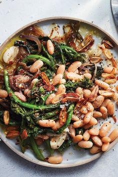 NYT Cooking: This white bean dish isn't shy when it comes to garlic. It's used in the pot along with the simmering beans, and also fried in olive oil as a crunchy, pungent garnish. As a contrast, the broccoli rabe and red onion get very sweet when you sauté them slowly until they are browned and caramelized. Alongside the soft, mild white beans, it's a satisfying and comforting...