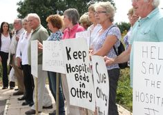 Save Our Hospitals - protesters at Newcourt Communtiy Centre this week. A controversial decision to cut community hospital beds in East Devon has come under fire from a district council watchdog.
