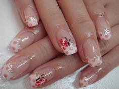 Classic looking French tip nails with a butterfly design. The design consists of a simple white French tip with pink polka dots and a red and black butterfly detail painted on top of it. Silver sprinkles are also added as lining for the French tip.
