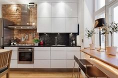 I am a fan of the combination if the high gloss cabinets with the natural wood and brick and a touch of black rock for the backsplash!