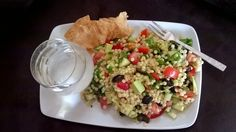 Gorgeous couscous salad with avo, tomato, red pepper, cucumber, spinich and olives. Sided with toasted wrap and a glass of water.