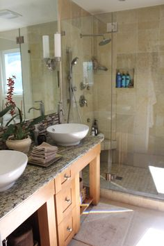 This master bath may be small but it is fully outfitted with two sinks atop a granite counter and a shower with tumbled Travertine marble walls, a custom glass door and water-saving fittings.