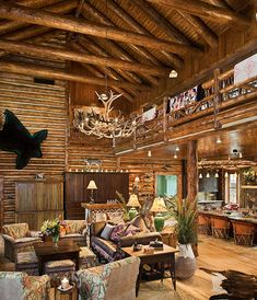 Great room has soaring ceilings with log rafters and log ties.  The loft area is located above and the custom twig railing system is found along the perimeter.
