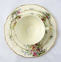 Made by A G Richardson & Co Ltd, Crown Ducal Florentine trio in the Rosalie pattern. Embossed creamware tea cup, saucer, and plate, are a soft cream colour with bright, intricate floral designs and gold trimming. The handle is painted with beautiful multi-coloured flowers. This pattern