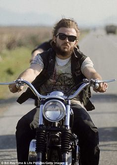 Member of Hell's Angels riding motorcycle on road