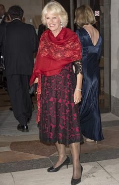 Camilla, Duchess of Cornwall wore a black and scarlet lace dress paired with a vibrant scarf and coiffed hair.    She is holding her black clutch and wearing black heels